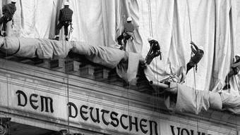 """ARCHIV - Gewerbekletterer rollen die Verhüllungsplanen für den Berliner Reichstag vom Giebel des Bauwerks ab. Direkt über dem Haupteingang und der Schrift """"Dem Deutschen Volke"""" fällt bei der Aktion des Verpackungskünstlers Christo der Stoff entlang der Säulen zu Boden. Foto: Wolfgang Kumm/dpa"""