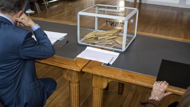 Beamte warten in einem Lokal in Villefranche-sur-Saône auf Wähler