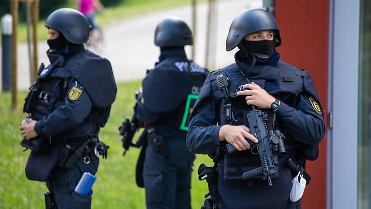 Beamte der Bereitschaftspolizei stehen vor einer Mehrzweckhalle, in der am Nachmittag eine Pressekonferenz zum Stand der Ermittlungen stattfinden soll. Ein Großaufgebot der Polizei sucht seit Sonntag einen bewaffneten Mann, der während einer Polizeikontrolle die Beamten bedroht und ihnen die Waffen abgenommen hatte. Nach der Tat am 12.07.2020 war er in den Wald geflüchtet.