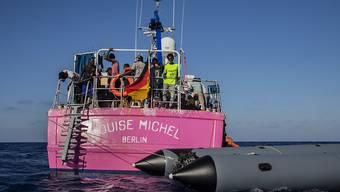 Migranten stehen an Bord des Rettungsschiffes «Louise Michel». Foto: Santi Palacios/AP/dpa
