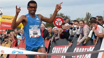 Der Schweizer Langstrecken-Spezialist Tadesse Abraham überquert die Ziellinie beim 40. Hallwilerseelauf als Erster und feiert seinen Sieg.