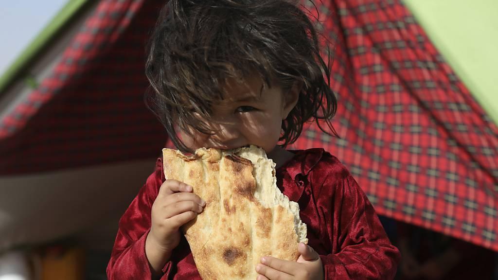 Ein afghanisches Mädchen, das aufgrund von von Kämpfen zwischen den Taliban und afghanischen Sicherheitskräften aus ihrer Heimat geflohen ist, steht vor einem Zelt in Masar-e Scharif und isst Brot. Foto: Rahmat Gul/AP/dpa