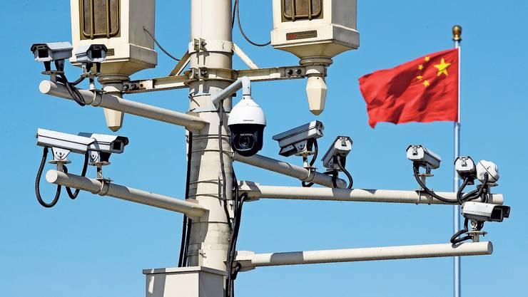 Chinesische Flagge hinter Überwachungstechnik Peking exportiert fleissig Überwachungssysteme.