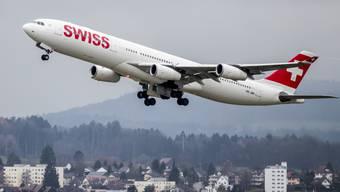 Ein Swiss-Flugzeug hebt ab am Flughafen Zürich - im Hintergrund die Gemeinde Rümlang.