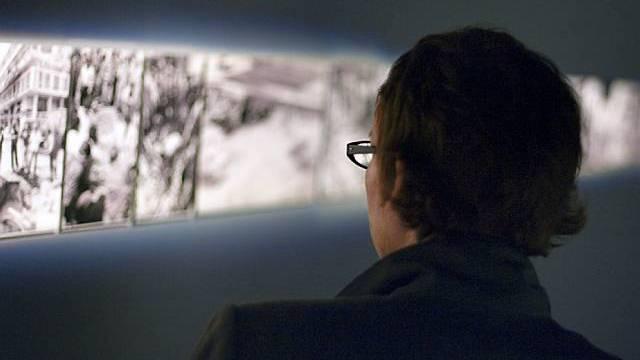 """Ein Mann betrachtet Bilder zu """"The Atlas Group"""" von Walid Raad (Archiv)"""