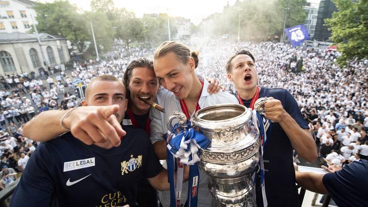 Die Mannschaft des FC Zürich feiert mit den Fans auf dem Zürcher Helvetiaplatz – im Bild: Marco Schönbaechler, Adrian Winter, Michael Frey und Cédric Brunner jubeln mit dem Pokal.