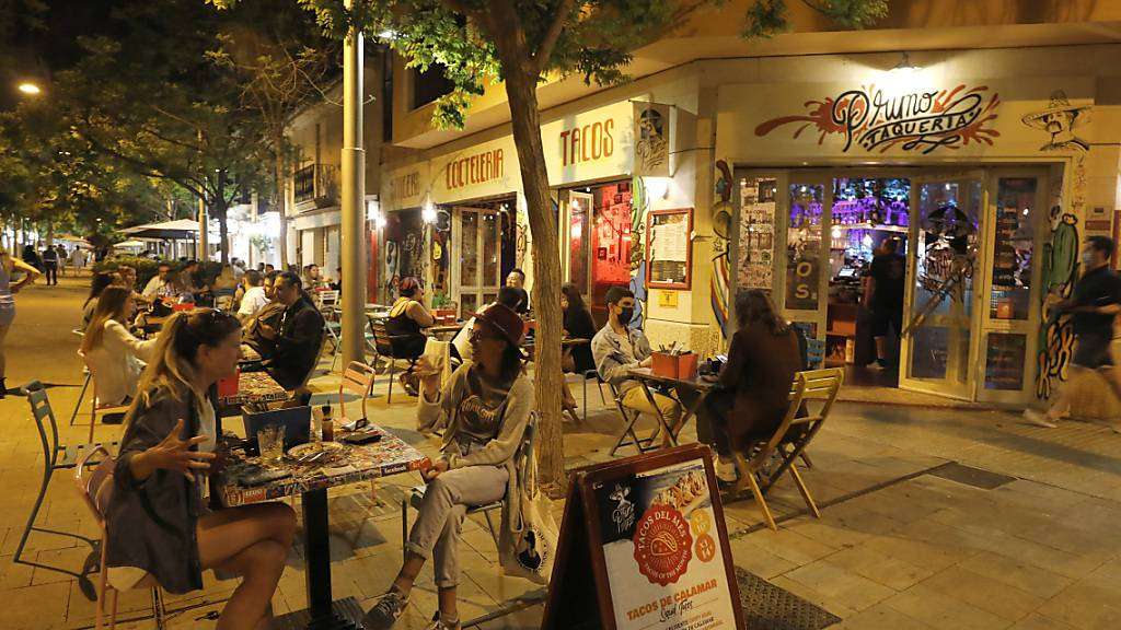 Kunden sitzen auf der Terrasse einer Bar. Foto: Clara Margais/dpa