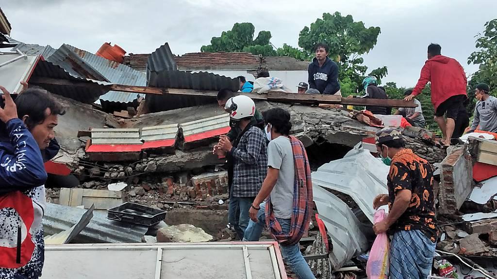 Anwohner auf der Insel Sulawesi inspizieren ein zerstörtes Haus. Foto: Yusuf Wahil/AP/dpa