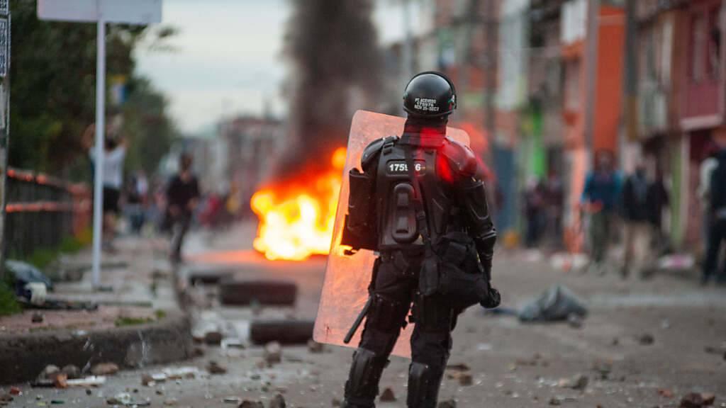 Protest gegen die vorgeschlagene Steuerreform: Ein Bereitschaftspolizist steht in Schutzausrüstung auf einer verwüsteten Straße in Bogotá. Foto: Chepa Beltran/VW Pics via ZUMA Wire/dpa
