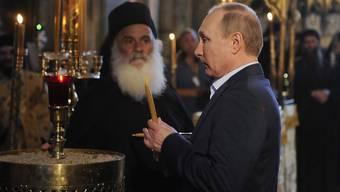 Der russische Präsident Putin zündet eine Kerze in einer Kirche auf Berg Athos an.