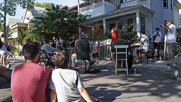 Menschen verfolgen die Veranstaltung «Make Music-New York». Aufgrund der Coronavirus-Pandemie traten verschiedene Musiker bei einem Freiluftkonzert auf, um für die Anwohner zu musizieren. Foto: Kathy Willens/AP/dpa