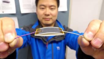 EPFL-Doktorand Xiao-Sheng Zhang mit seinem System: Ein Sandwich aus Graphit-bemaltem Papier und Teflonband erzeugt beim Zusammendrücken ein Ladungsgefälle. Beim Loslassen nimmt das Graphit die Ladung auf und leitet sie ab.