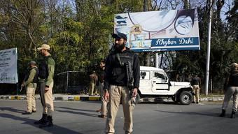 Indische Polizisten stehen an einer Strasse in Srinagar Wache, die zum Regierungsgebäude führt. Dort legte der neue Gouverneur von Jammu und Kaschmir den Amtseid ab.