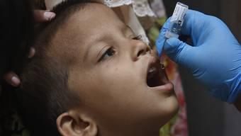 Ein Mitarbeiter des Gesundheitswesens verabreicht einem Kind einen Polio-Impfstoff. Nach Monaten der Unterbrechung durch die Corona-Pandemie hat in Pakistan erstmals wieder eine Impfkampagne gegen Kinderlähmung begonnen. Foto: Fareed Khan/AP/dpa