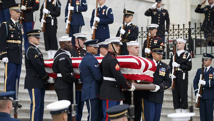 Der mit der US-Flagge bedeckte Sarg des verstorbenen US-Präsidenten George H. W. Bush wird unter militärischem Zeremoniell aus dem Kapitol herausgetragen.