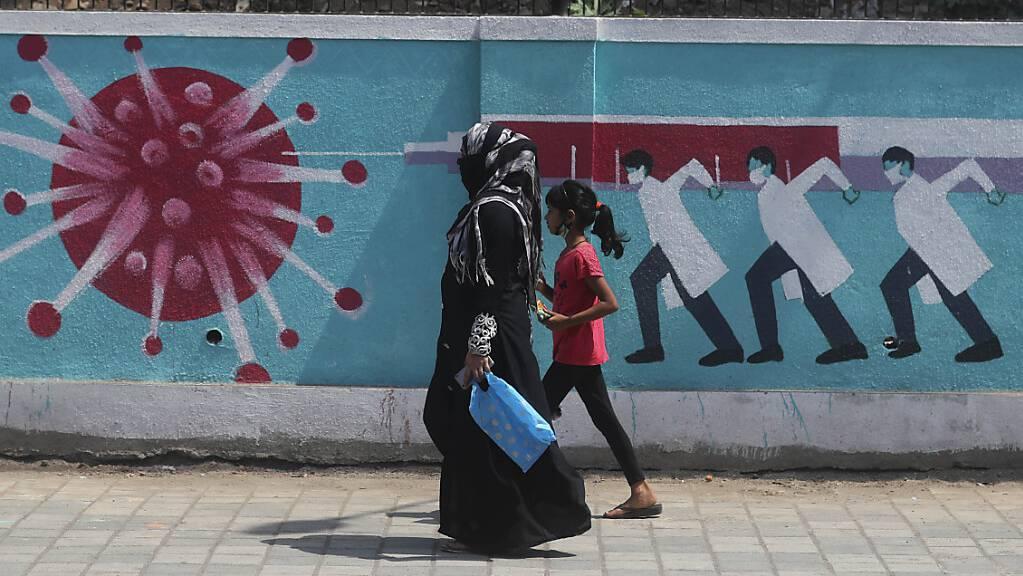 Eine Frau geht zusammen mit einem Mädchen an einem Graffiti vorbei, das das Coronavirus darstellt. Foto: Rafiq Maqbool/AP/dpa