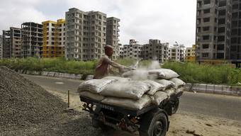 Ein indischer Arbeiter beläd eine Motor-Rikscha mit Zementsäcken auf einer Baustelle in Kalkutta: Der Abschwung macht den Zementherstellern sorgen.
