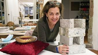 Dora Freiermuth mit der Krone aus leeren Nespresso-Kapseln, die sie 2019 anlässlich einer Ausstellung zum 1000-Jahr-Jubiläum des Basler Münsters geschaffen hat, und den Backsteinen aus Zeitungspapier.