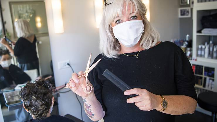 Die Lausanner Coiffeuse Sonia Cottini an der Arbeit: Die Gesichtsmasken seien störend, aber sie werde sich daran gewöhnen müssen, sagt sie.