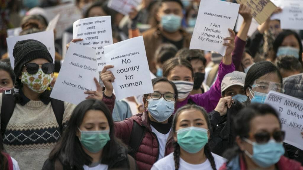 """ARCHIV - Nepalesische Frauenrechtsaktivistinnen halten bei einem Protest Schilder mit der Aufschrift #rageagainstrape - No country for women"""" (Wut auf Vergewaltigung - Kein Land für Frauen) hoch. Foto: Niranjan Shrestha/AP/dpa"""