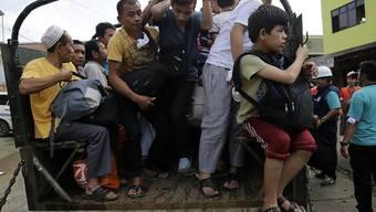 Flüchtende zwängen sich auf ein Fahrzeug, um den Kämpfen zu entkommen.
