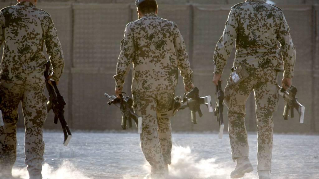 ARCHIV - Deutsche Bundeswehrsoldaten tragen Waffen zum Depot. Foto: picture alliance / dpa