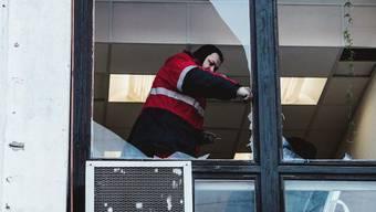 Aufräumen nach dem Meteoriten-Einschlag: Mann in Tscheljabinsk schlägt geborstene Scheiben aus dem Fensterrahmen