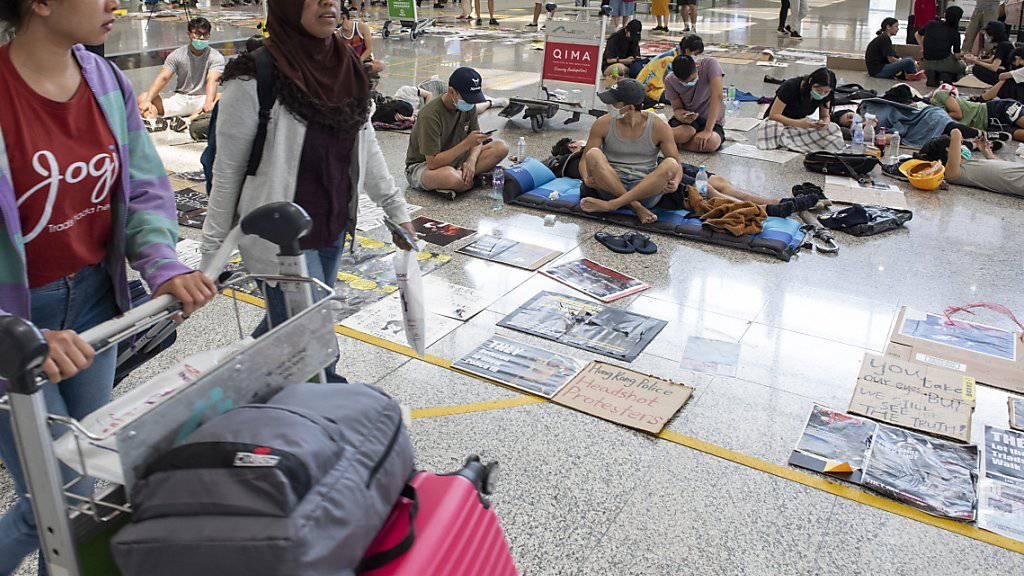 Passagiere gehen am Flughafen von Hongkong an Protestierenden vorbei.