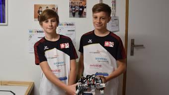 Jakob Hechler (links) und Nicola Alessandrelli zeigen ihren Lego Mindstorm-Roboter. Passend zu ihrem Auftritt: Eigene T-shirts mit dem Schweizer und dem Erlinsbacher Wappen.