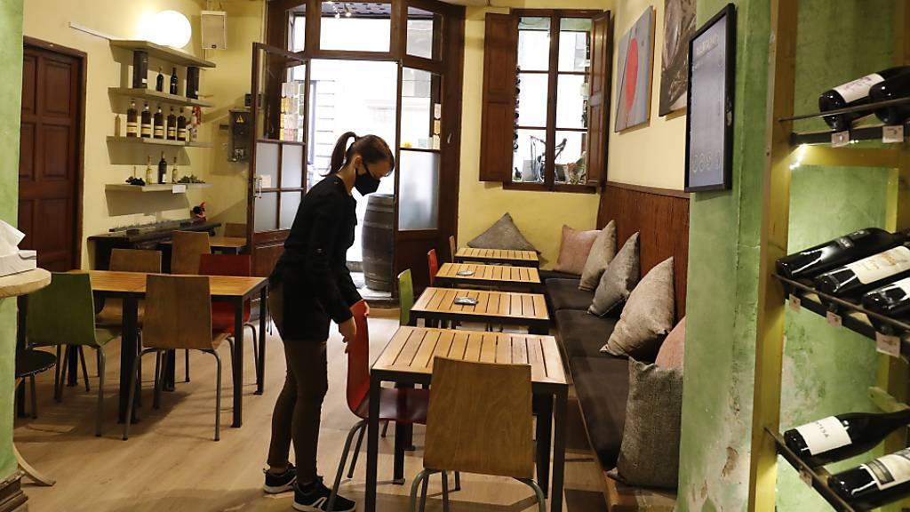 ARCHIV - Eine Kellnerin mit Maske bereitet in Palma den Innenraum eines Restaurants für das Tagesgeschehen vor. Foto: Clara Margais/dpa