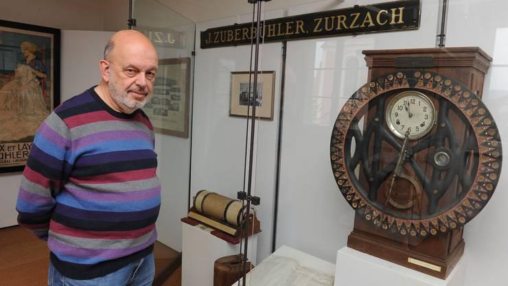 Ausstellungsmacher Fredi Hidber vor der Stempeluhr aus einer Fabrik Jakob Zuberbühlers.  Angelo Zambelli
