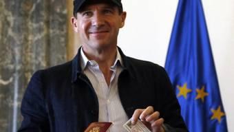 Ralph Fiennes mit seinem neuen serbischen Pass und der Identitätskarte.