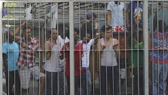 Bald jeder unter Generalverdacht? Asylbewerber stehen hinter dem Tor des Flüchtlingsempfangszentrums in Chiasso im Kanton Tessin. Karl Mathis/Key