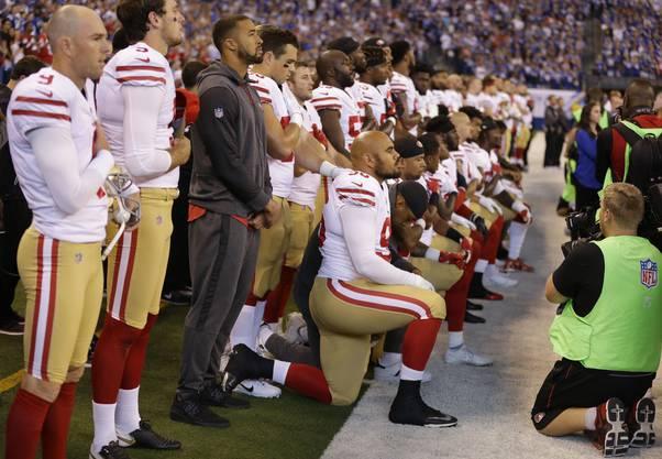 Die San Francisco 49ers beim Knien während der Nationalhymne. Ihr ehemaliger Teamkollege und Quaterback Colin Kaepernick hatten den Protest gegen Rassismus und Polizeigewalt gegen Schwarze im August 2016 initiiert.