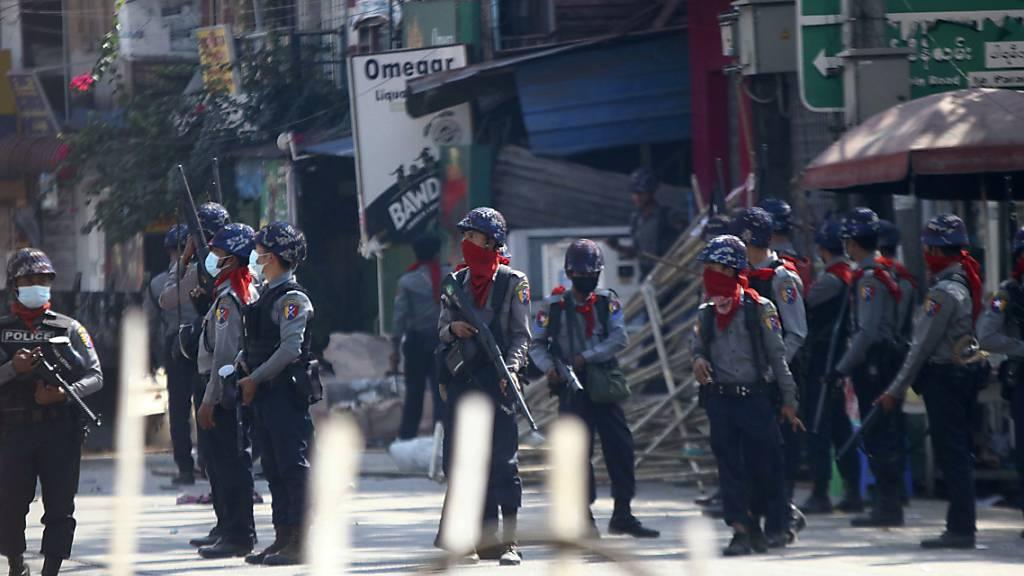 Bewaffnete Polizisten stehen auf einer Straße, um eine Demonstration gegen den Militärputsch zu verhindern. Foto: Str/AP/dpa
