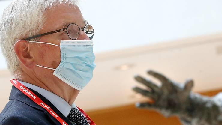 Mit Mund- und Nasenschutzmaske und einem Band mit der Internetadresse der SPD steht Thilo Sarrazin im Atrium des Willy-Brandt-Haus neben der Statue von Willy Brandt und wartet auf den Beginn der Verhandlung. Foto: Wolfgang Kumm/dpa