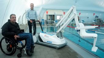 Direktor Urs Jäggi hat den Lift an den Bassinrand geschoben. Rollstuhlfahrer Achim Bader erhält für die Nutzung des Badelifts Assistenz vom Personal.