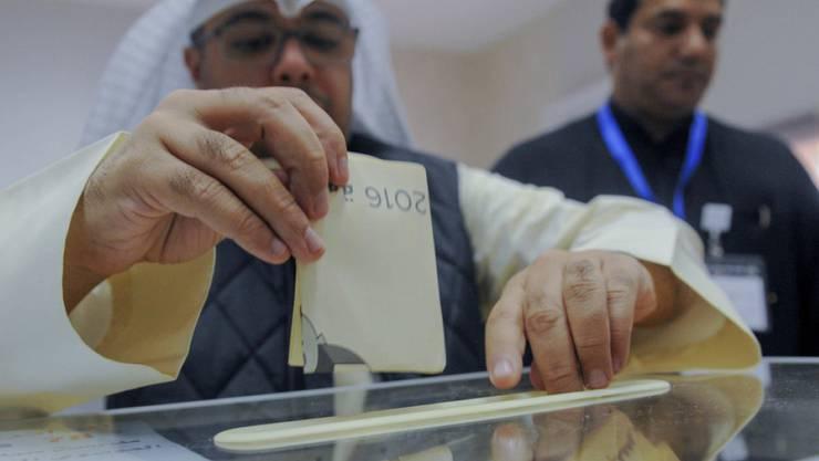 Ein Mann gibt in einem Wahllokal in Kuwait City bei der vorgezogenen Parlamentswahl seine Stimme ab.