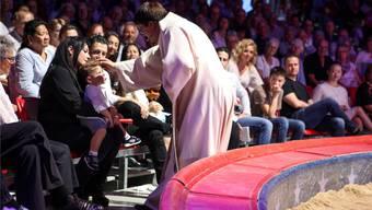 Zirkuspfarrer Adrian Bolzern tauft Maycol junior auf dem Schoss seiner Mutter Géraldine Knie – dahinter Vater Maycol Errani.