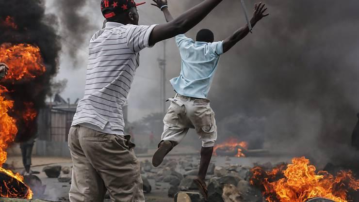 Demonstranten springen über brennende Barrikaden in Burundis Hauptstadt Bujumbura