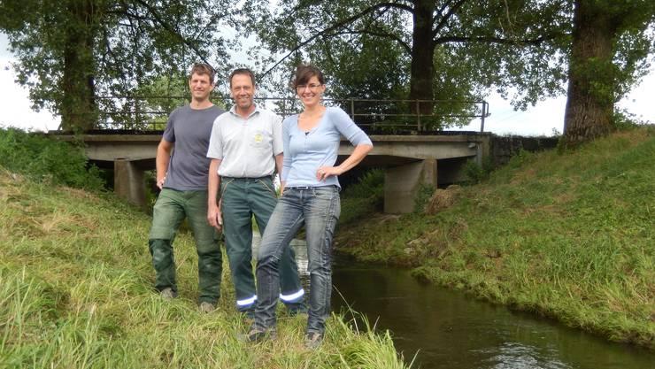 Bio-Bauer Adrian Knuchel (l.) und der konventionelle Bauer Beat Wyss mit Martina Jenzer, Fachfrau für Pflanzenschutz, vor dem träge dahinfliessenden Limpach.