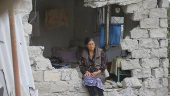 Eine Frau sitzt nach einem Beschuss der armenischen Artillerie inmitten der Trümmer ihres Hauses. Russland hat nach neuen Kämpfen die beiden verfeindeten Nachbarn Armenien und Aserbaidschan an die strikte Einhaltung der ausgehandelten Waffenruhe für die Unruheregion Berg-Karabach erinnert. Foto: Aziz Karimov/AP/dpa