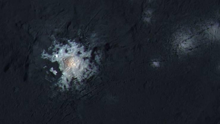Kontrastverstärktes Bild des hellen Flecks im Occator Krater auf Zwergplanet Ceres. Eine hochauflösende Aufnahme vom Februar 2016 wurde hierfür mit Farbbildern kombiniert, welche die Raumsonde Dawn bereits im September aufgenommen hatte.