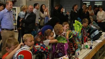 Nach dem feierlichen Einzug ins Feuerwehrlokal Rütihof packen die neuen Erstklässler ihren neuen Schulthek aus – beobachtet und manchmal unterstützt von den Eltern.