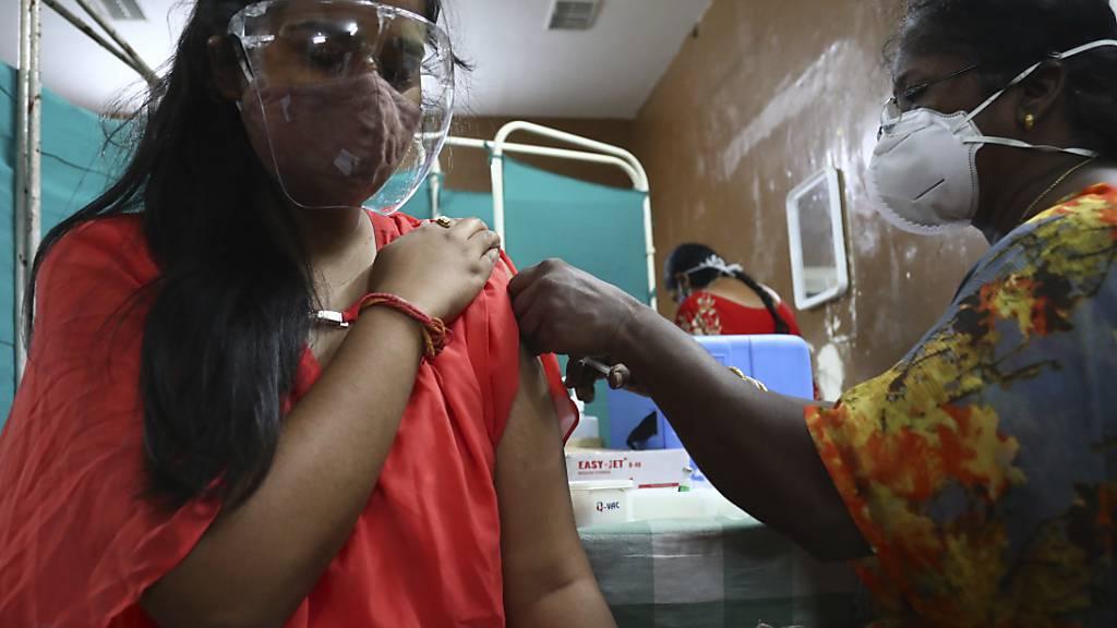 Eine Mitarbeiterin des Gesundheitswesens verabreicht einer Frau eine Dosis von Covishield, der Version des Impfstoffs von Astrazeneca. Foto: Mahesh Kumar A/AP/dpa