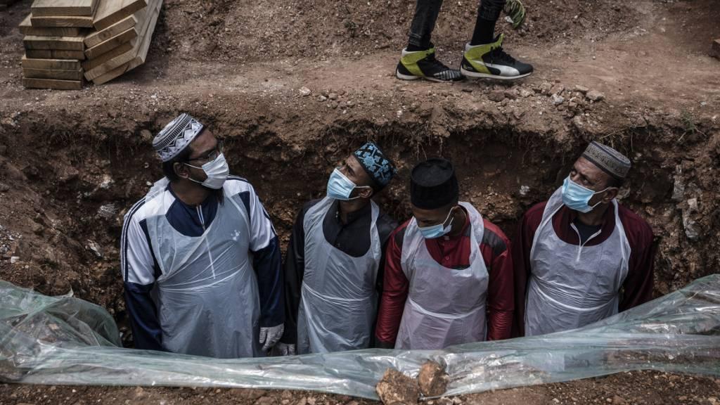 dpatopbilder - Bestatter in Schutzkleidung bereiten das Grab für eine an dem Coronavirus verstorbenen Person auf dem Avalon-Friedhof in Johannesburg für die Beerdigung vor. Foto: Shiraaz Mohamed/AP/dpa