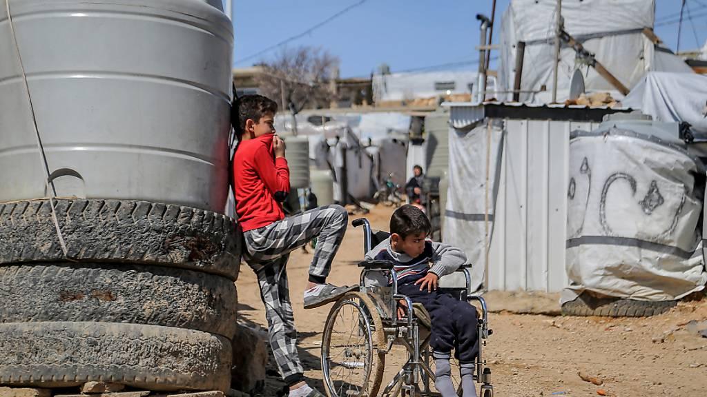 Ein syrischer Junge steht neben seinem Bruder, der im Rollstuhl sitzt, im Flüchtlingslager Barra nordöstlich der libanesischen Hauptstadt Beirut. Foto: Marwan Naamani/dpa