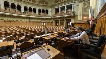 Leere Reihen im Nationalratssaal: Philippe Schwab, Generalsekretär der Bundesversammlung, packt seine Sachen. Die Session ist abgesagt.