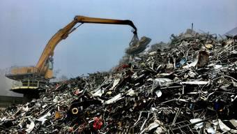 Das Autowrack wird auf einen Haufen Metallschrott gehievt: Szene auf dem Areal der Wiederkehr Recycling AG in Waltenschwil.