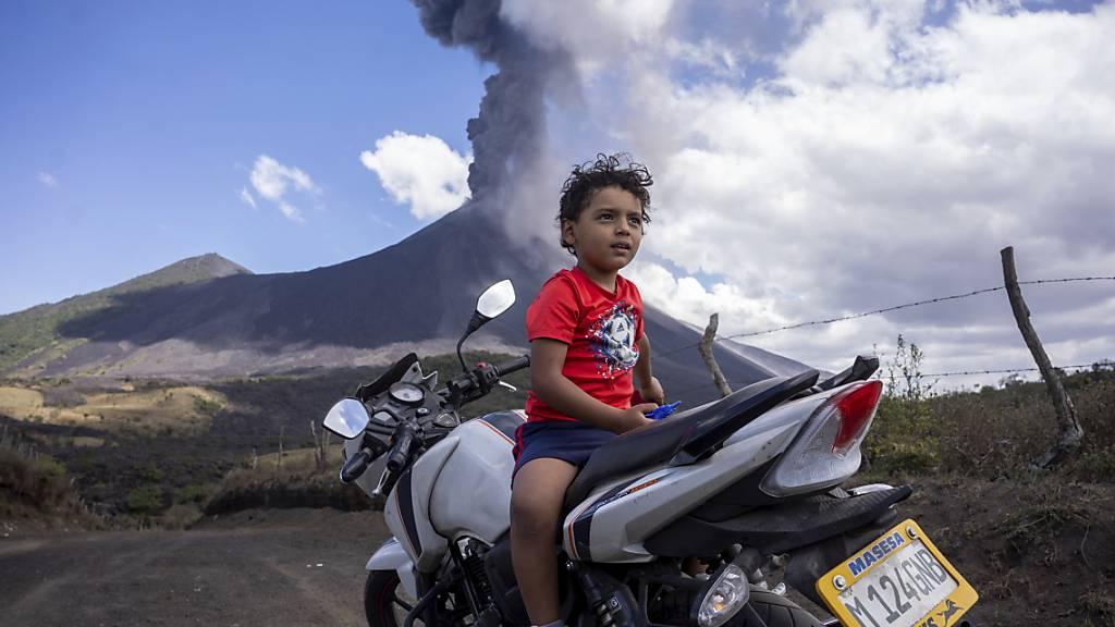 Ein Kind sitzt auf einem Motorrad, während im Hintergrund der Vulkan Pacaya ausbricht. Zum zweiten Mal innerhalb von drei Tagen ist der Vulkan Pacaya in Guatemala ausgebrochen. Foto: Santiago Billy/AP/dpa